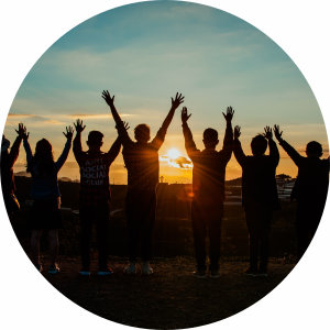 Image of a group of people with hands up facing the sunrise.